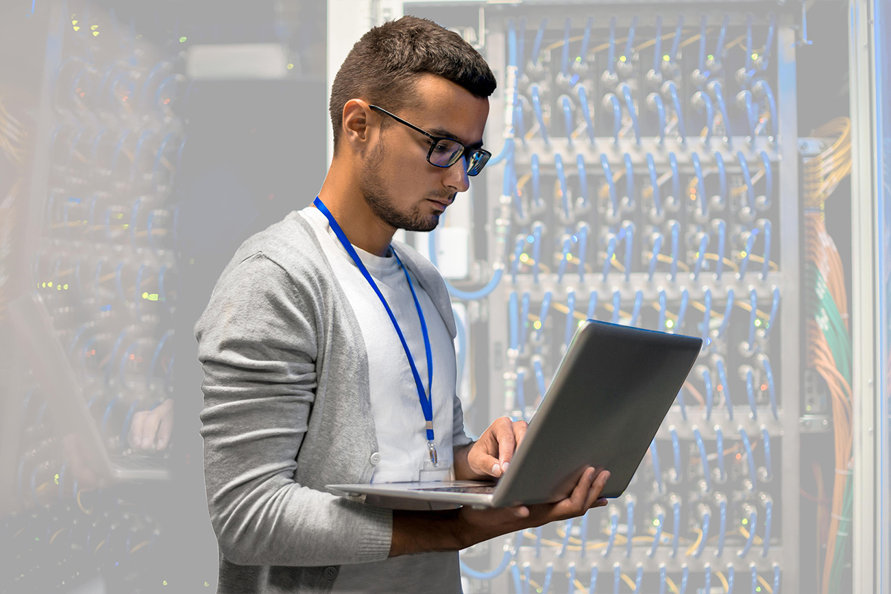 IT worker holding laptop computer in a server room